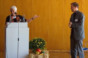 Prof. Dr. Irmgard Merkt steht links hinter dem Rednerpult und stellt André Necke vor.