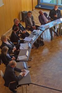 Acht Teilnehmer und Teilnehmerinnen der Podiumsrunde im Gespräch.