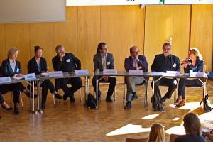 Foto von sieben der acht Diskutanten der Podiumsrunde.