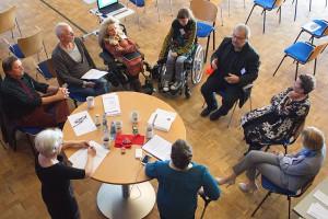 """In einem Kreis sitzen und stehen die Workshop-Teilnehmerinnen und Teilnehmer zum Thema """"Freiberufliche Kunst- und Kulturschaffenden mit Behinderung"""""""