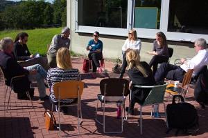 Vor der Akademie sitzen die Workshop-Teilnehmer und Teilnehmerinnen in einer Arbeitsrunde zusammen.