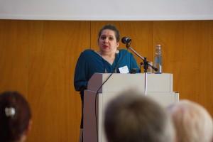 Auf dem Bild steht Annton Beate Schmidt am Rednerpult und gibt eine Einführung in ihr Workshop-Thema..