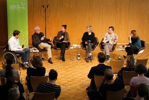 Sechs DiskutantInnen sitzen in der Akademie vor Publikum.
